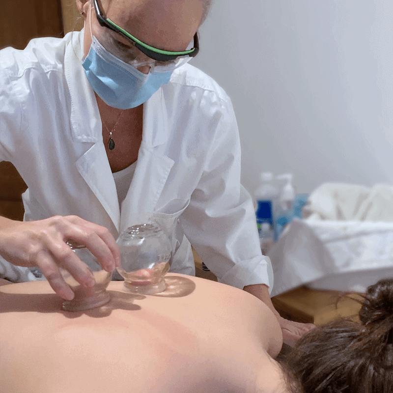 Marie-Andrée Saint-Pierre traitant une patiente à l'aide de ventouse thérapeutiques et portant des lunettes de sécurité, un masque et un sarreau